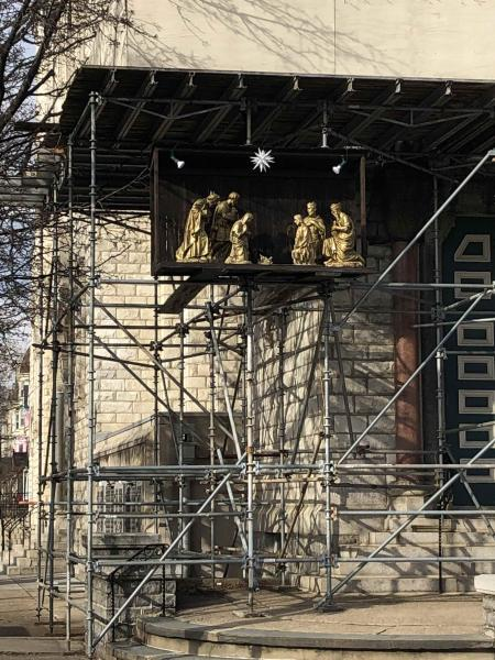 scaffolding on a building with a lofted nativity scene among it