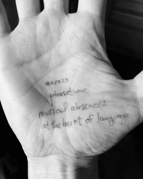 "Person's palm with words written in pen on it: ""across / phasetime / musical absences / at the heart of language."""