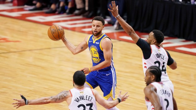 Steph Curry playing basketball, facing three defenders