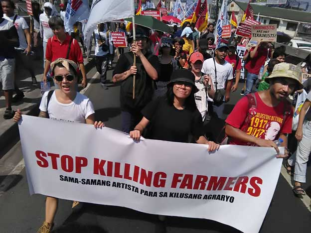Peasant advocates who work in the art, culture, and knowledge industries march together as SAKA (Sama-samang Artista para sa Kilusang Agraryo or Artists' Alliance for Genuine Agrarian Reform) on Labor Day, carrying a banner that calls on the state to stop killing farmers. As of this writing, 202 farmers have been killed under the US-Duterte regime in relation to land disputes since he came to power in 2016. The author is one of the marchers carrying the banner. (Photo courtesy of Yo Salazar and SAKA.)