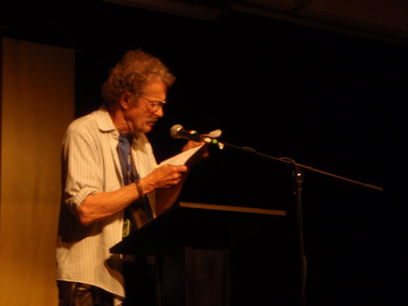 a photograph of the poet Jack Collom reading at Naropa University in June of 2011