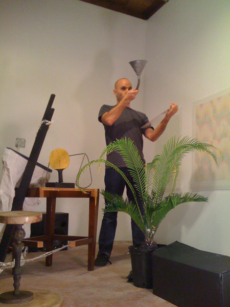 Marcus Civin performing in front of a drawing by Peter Wilson in the studio in the backyard