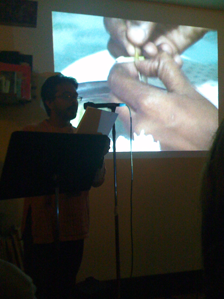 Amar Ravva performing excerpts from his forthcoming book American Canyon alongside projections, in the front room.