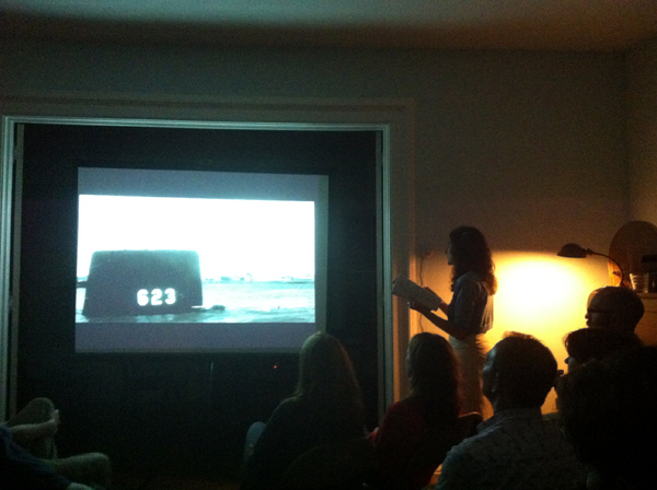 "Jen Hofer performing a live film narration piece with an image from the film ""On The Beach"" at an Evening of Various Wonders (inspired by those on Elm Street) at the home of Anna Moschovakis and Trevor Wilson in South Kortright, NY."