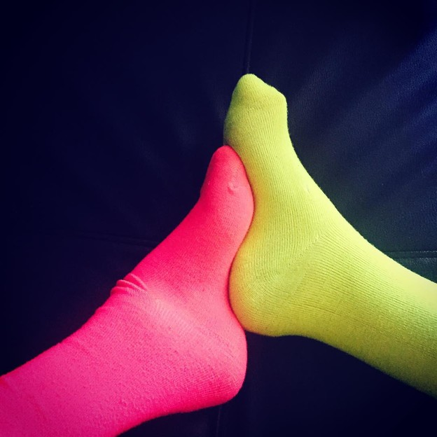 Two high-arched club feet in neon socks, one pink and one yellow, interlock.