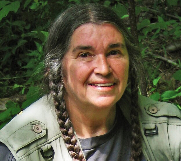 Bernadette Mayer smiling at the camera with her hair in braids