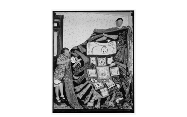 Black and white image of a woman and man holding a large quilt.